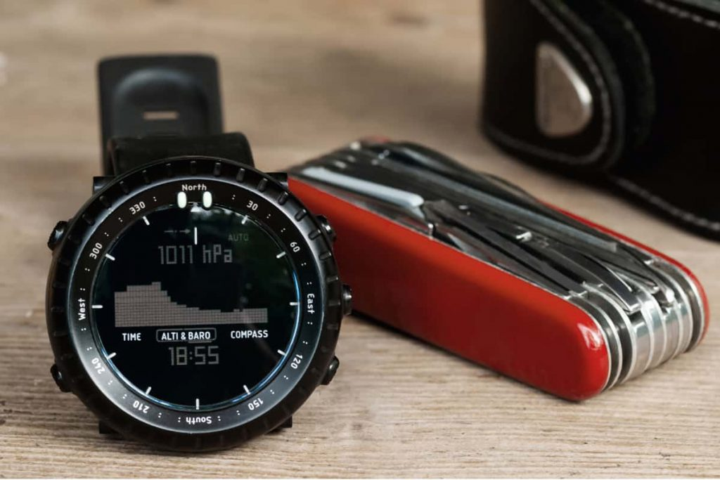 Closeup of hiking wrist watch and multipurpose knife on wooden table