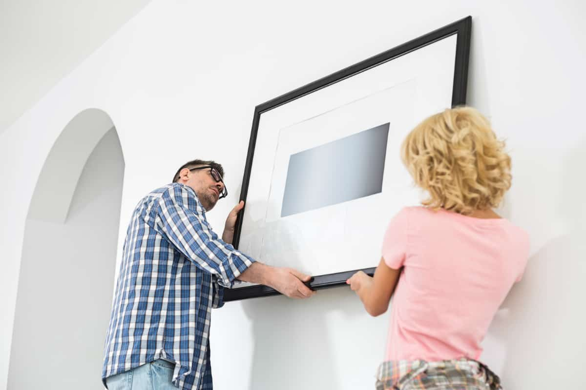 Couple hanging picture frame on wall in new house