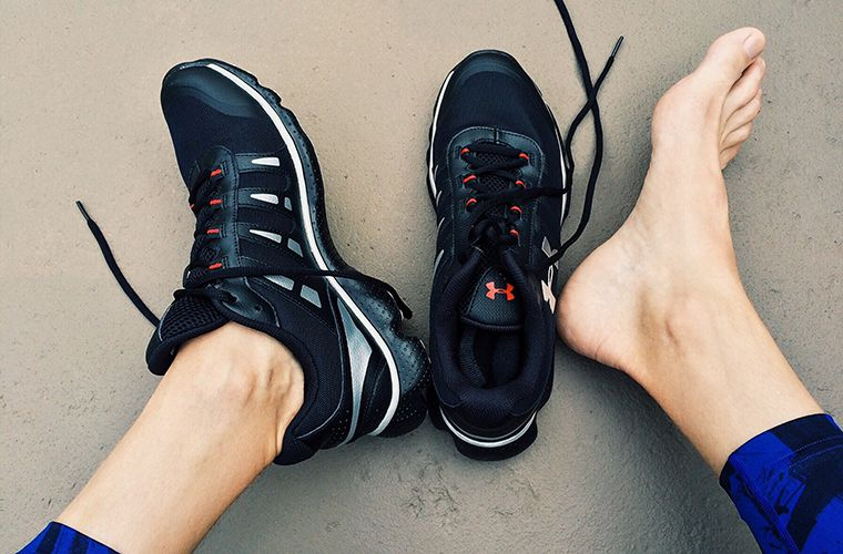 man's feet with one running shoe on and one off