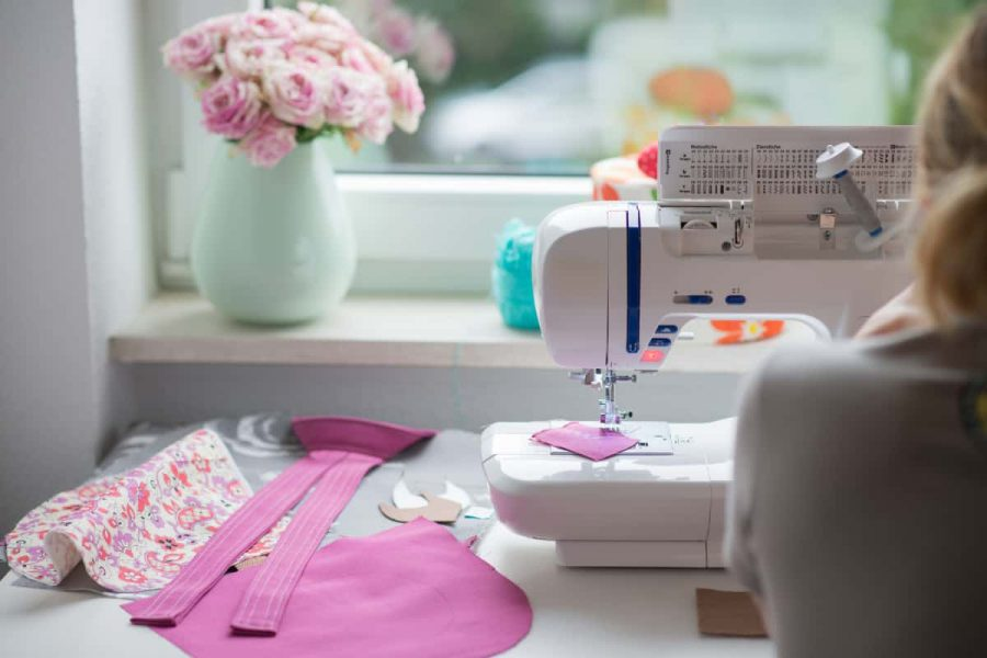View of sewing room with sewing machine, fabric, flowers and a woman.