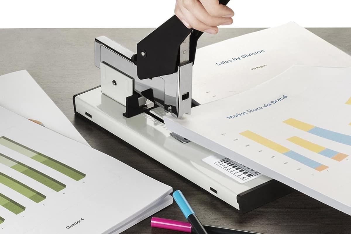 A woman stapling a big stack of paper with a heavy-duty stapler