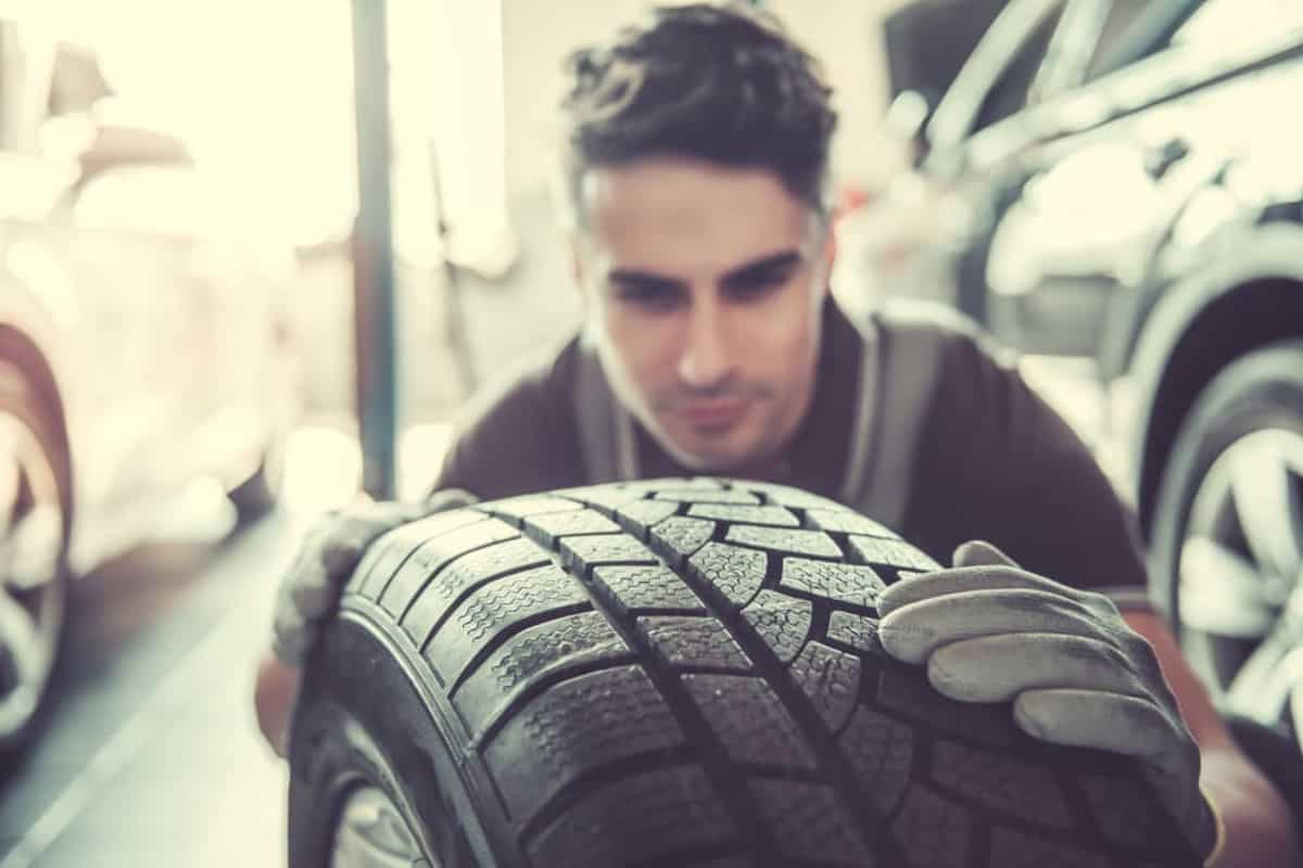 man inspecting a car tire