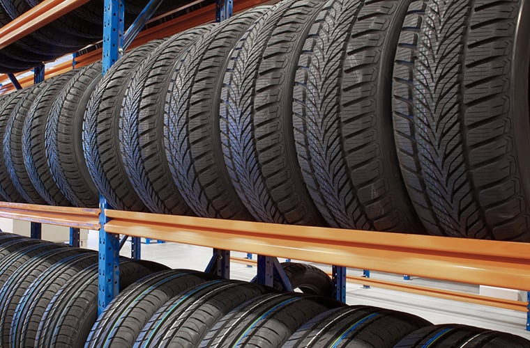 warehouse storing car tires in rows for sale