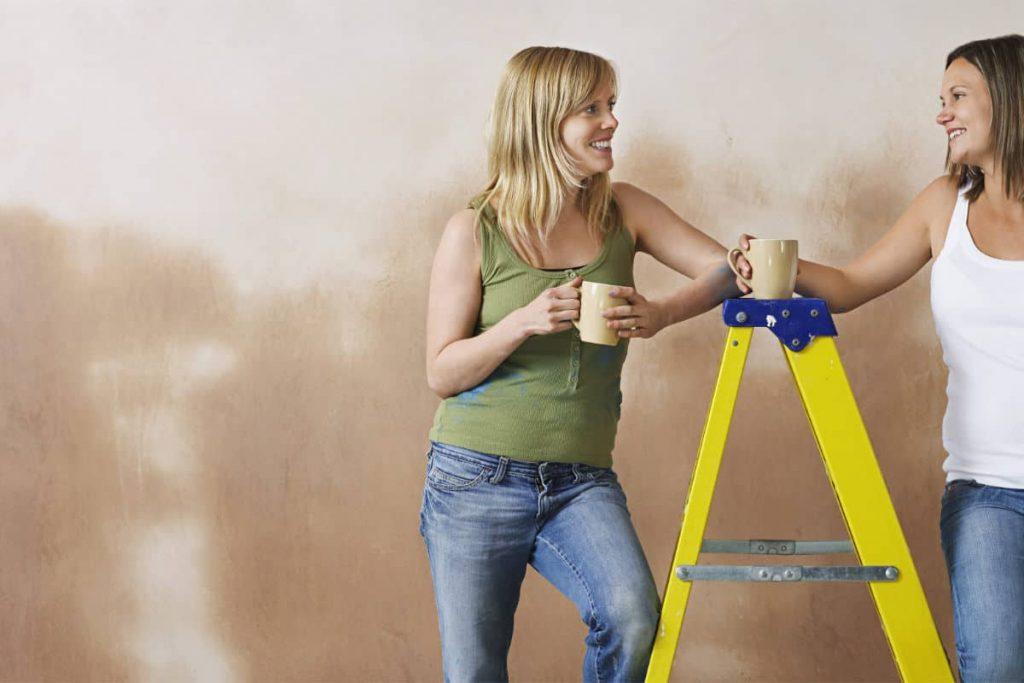 two women leaning on a heavy duty step ladder