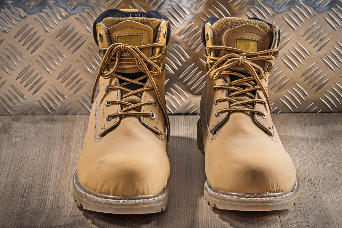 waterproof and durable work boots on wooden board with corrugated metal plate in the background
