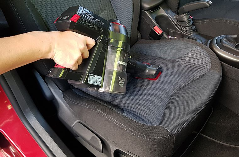 Vacuuming a car seat with a battery vacuumer