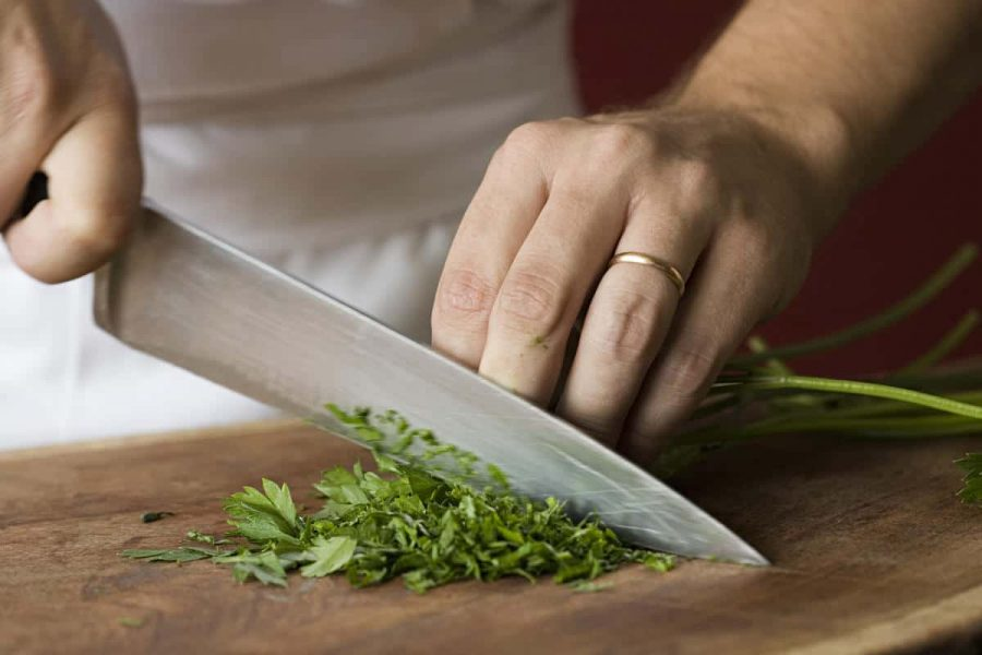 Chef chopping parsley on a wooden board