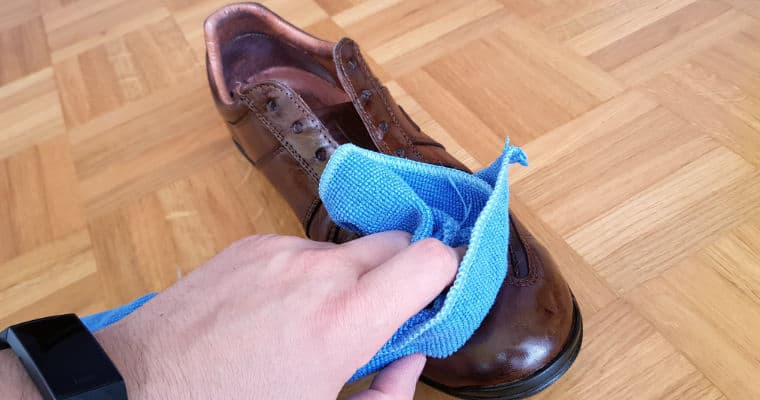 cleaning a brown leather shoe with a damp cloth
