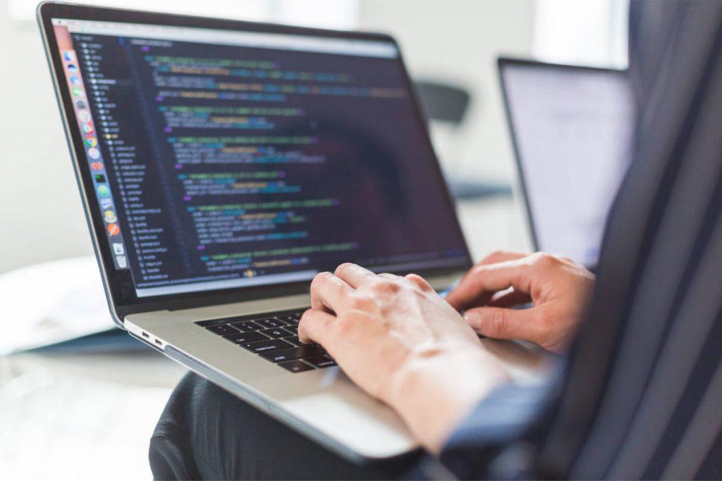 man coding on a laptop