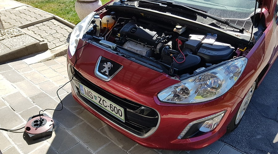 The front of Peugeot 308 with a CTEK MXS 5.0 charger attached to the battery