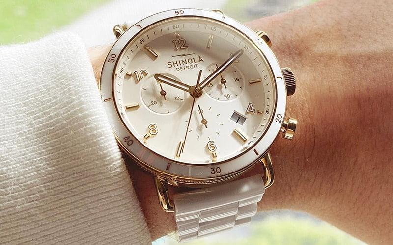 woman's wrist with a shinola watch