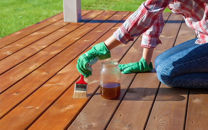 Woman applying protective varnish on a wooden deck