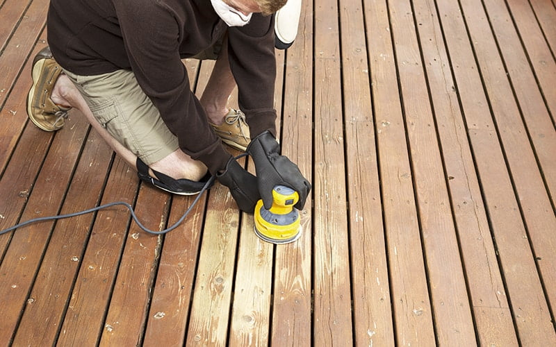 Man performing maintenance on home wooden deck