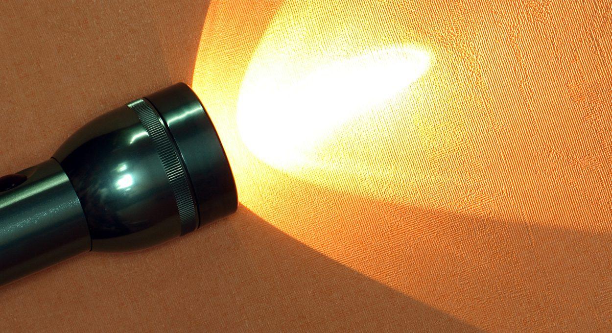 Modern aluminium luminous flashlight on ginger background with copy space