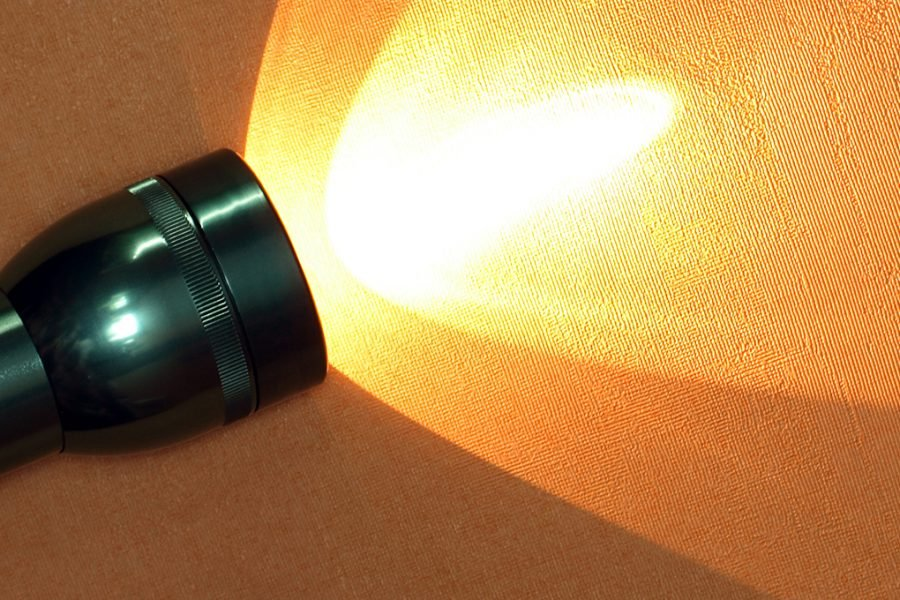 Modern aluminium luminous flashlight on ginger background with copy space
